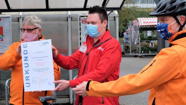Vorstandssprecher Herbert Fürmann (links) und Jörg Walther (rechts) vom ADFCüberreichten die Urkunde an Toom-Marktleiter Matthias Schwucht.