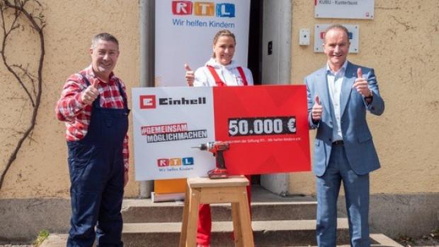 Joachim Llambi (von links), Simone Mecky-Ballack und Andreas Kroiss übergaben in München den Spendenscheck.