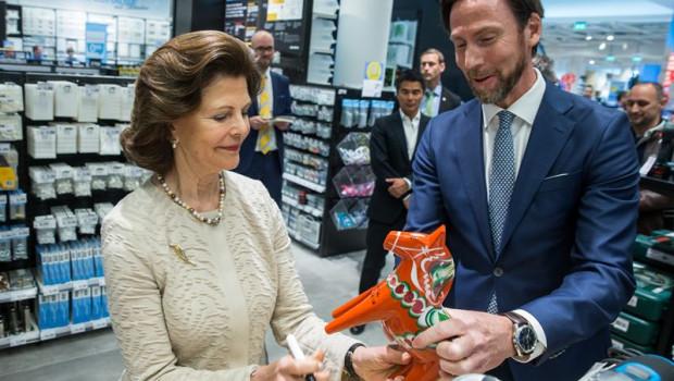 Königin Silvia wurde von Clas Ohlson-Chef Klas Balkow begrüßt und signierte im neuen Markt ein Dalapferd.