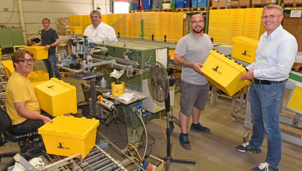 Die Siebdruckmaschinebedient Andreas Knoblach (links), seineKollegen Matthias Weyell (2 v. l.) und Sebastian Meißner (2. v. r.) stellen die Boxen aufsRollband und die Paletten.