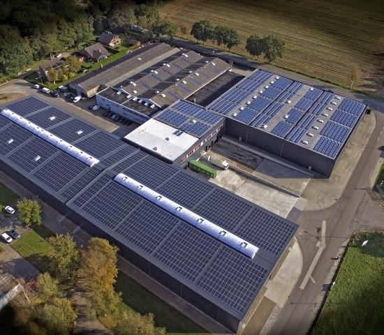 Die Vogelperspektive macht die Dimensionen der Erweiterung in Westerstede erkennbar. Vorne im Bild ist der 5.600 m² große Neubau erkennbar; das Dach ist fast vollständig von einer Photovoltaikanlage bedeckt.