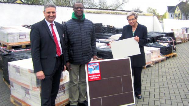 Dr. Samuel Okae (M.) und Hannelore Bauer haben die mehr als 2.000 m² Fliesen von Hellweg-Marktleiter Martin Niewerth in Empfang genommen.