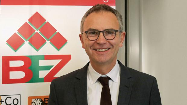 Hartmut Möller im Oktober 2017 bei der Bekanntgabe, dass sich Bauwelt und Holz+Co der Eurobaustoff anschließen. Das Logo der BEZ im Hintergrund ist nun bald Geschichte. [Bild: Eurobaustoff]
