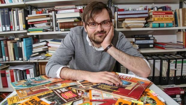 """Jonathan Voges vor einer Auswahl """"historischer"""" Heimwerkerzeitschriften (Foto: Leibniz Universität Hannover)."""