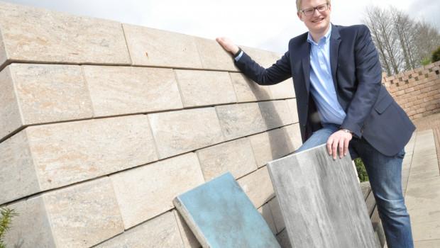 Geschäftsführer Theo Diephaus jr. mit seinem preisgekrönten Produkten, der Gartenmauer Tosa und der beschichteten Terrassenplatte Latio. Foto: Stefan Freiwald
